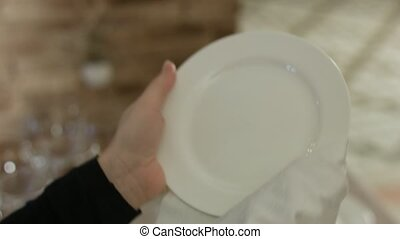 Waiter take plate from the table and wiping it