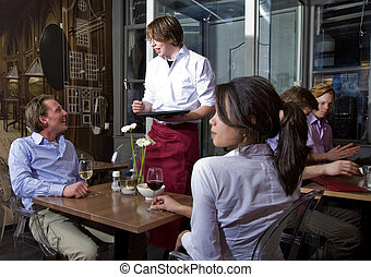 taking orders - waiter taking orders from a customer in a...