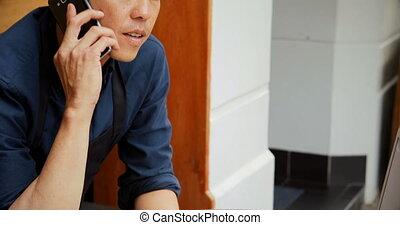 Waiter talking on mobile phone 4k - Waiter talking on mobile...
