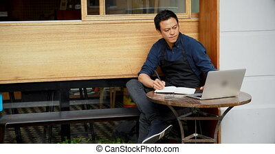 Waiter using laptop and writing on notepad 4k - Waiter using...
