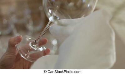 Waiter wiping wineglass to shine