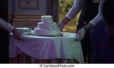 Waiter with white celebration cake at the party