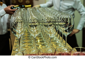 waiters pour champagne on glasses at a banquet