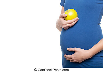 Waiting for a baby. Cropped image young pregnant woman touching her abdomen and holding apple while standing isolated on white