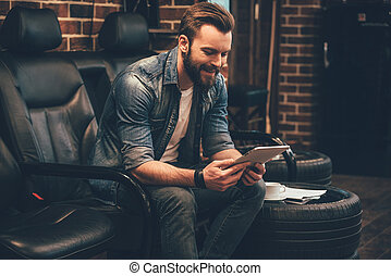 Waiting for appointment. Handsome young bearded man working on digital tablet with smile while sitting in comfortable chair at barbershop