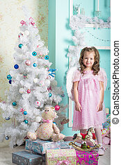 Waiting for Christmas: a little girl dresses up Christmas tree