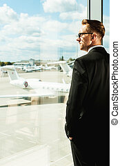 Waiting for flight. Rear view of thoughtful businessman in formalwear looking through a window in airport