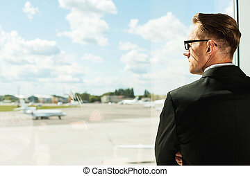 Waiting for his flight. Rear view of thoughtful businessman in formalwear looking through a window in airport