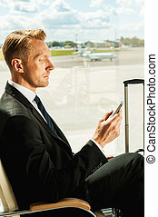 Waiting for his flight. Side view of confident businessman in formalwear holding mobile phone while waiting for a flight in airport