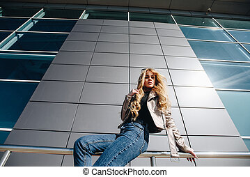 Waiting for inspiration. Cheerful young beautiful woman sitting on the parapet, hand behind head and looking with smile while, dreaming of rest day