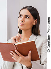 Waiting for inspiration. Thoughtful young businesswoman in suit holding note oad and touching her chin with pen while leaning at the wall