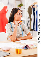 Waiting for inspiration. Thoughtful young woman holding hand on chin and smiling while sitting at the desk in fashion workshop