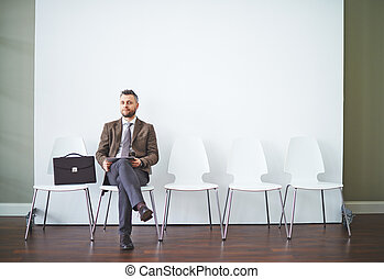 Confident man in formalwear waiting for his turn for interview