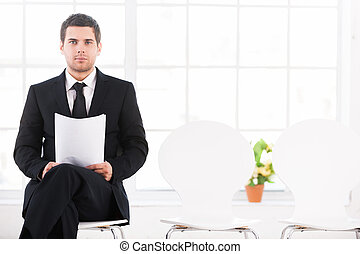 Waiting for job interview. Confident young man in formalwear sitting at the chair and holding head in hand while other chairs standing in a row