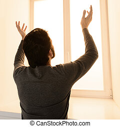Waiting for miracle. Rear view of man standing in front of the window with his hands raised up