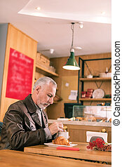 Grey-haired businessman waiting for business partner in French bakery