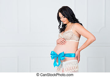 Waiting for son. Beautiful pregnant with a blue bow on her stomach