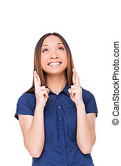 Waiting for special moment. Cheerful young woman looking up and keeping fingers crossed while standing isolated on white