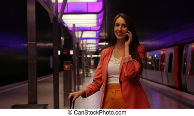Waiting for subway - a young business woman talking on smartphone and laughing