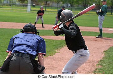 A batter crouches awaiting the pitch.