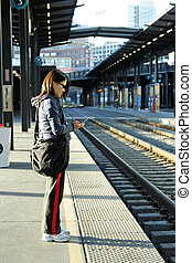 Waiting for the train - A young girl making a phone call ...