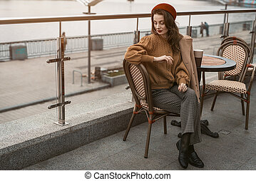 Waiting or frustrated french young woman sitting outdoors street restaurant looking frustrated down. Portrait of stylish young woman wearing autumn coat and red beret outdoors.