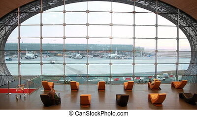 Waiting room in Paris airport with modern seating and window...
