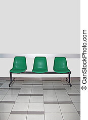 Waiting room - Empty waiting room with three green chairs...