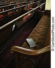 Waiting to worship - Bible on empty pew. Focused on bible....