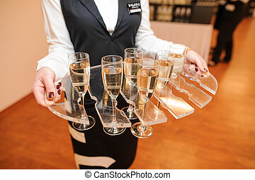 Waitress dressed in the uniform serving a set of champagne