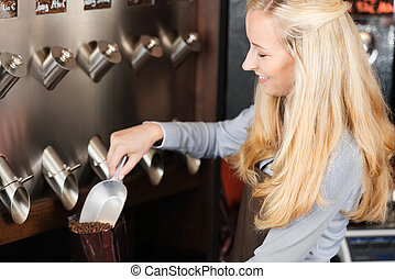waitress filling coffee beans in a bag