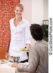 Waitress handing meal to customer