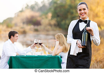 waitress holding a bottle of wine in front of customers