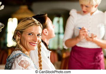 Waitress in Bavarian restaurant taking orders