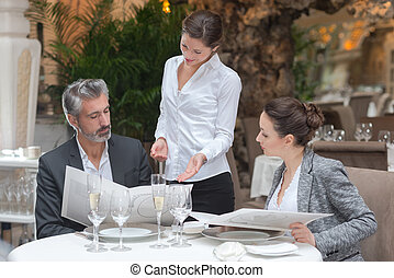 waitress offering tasty dishes to smiling guests couple