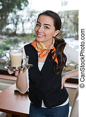 Waitress posing with cup of coffee in caf? or restaurant - ...