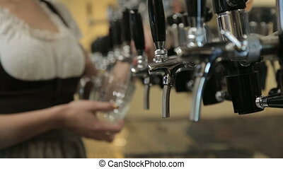 Waitress pours a beer from the beer tap in the pub