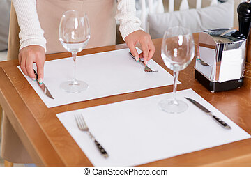 Waitress putting silverware for guests.