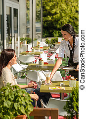 Waitress serve woman latte at cafe bar terrace sunny day