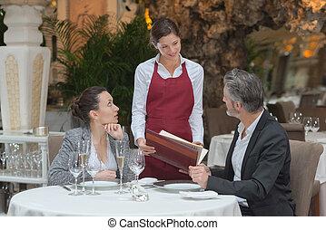 waitress serving a couple in a restaurant