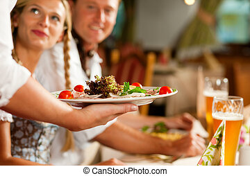 Waitress serving an Bavarian Restaurant - Couple in Bavarian...