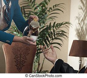 Waitress Serving Arabic Coffee to a Wealthy Arab Man