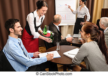 Waitress serving business people conference room