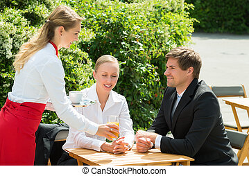 Waitress Serving Glass Of Juice To Businesspeople