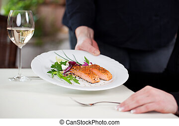waitress serving salmon on a restaurant table