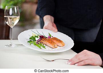 waitress serving salmon on a restaurant table