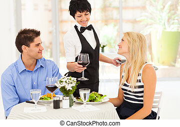 waitress serving wine to diners