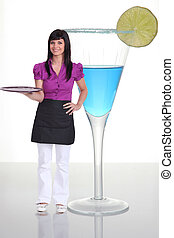 Waitress standing next to a human-sized cocktail