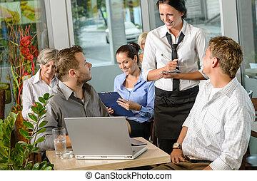 Waitress taking order from businessmen in cafe smiling...