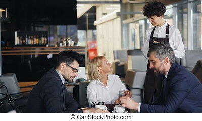 Waitress taking order from group of businesspeople men and...